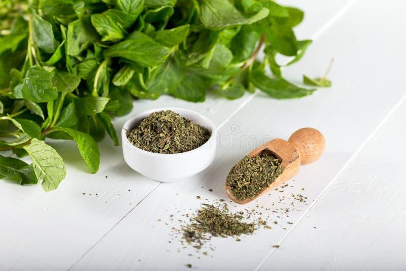 Droge pepermunt in een witte kom en een bos van verse munt, op houten achtergrond stock foto