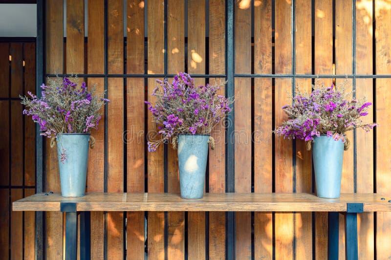 Droge purpere bloem in de decoratie van de zinkvaas op planken stock afbeelding