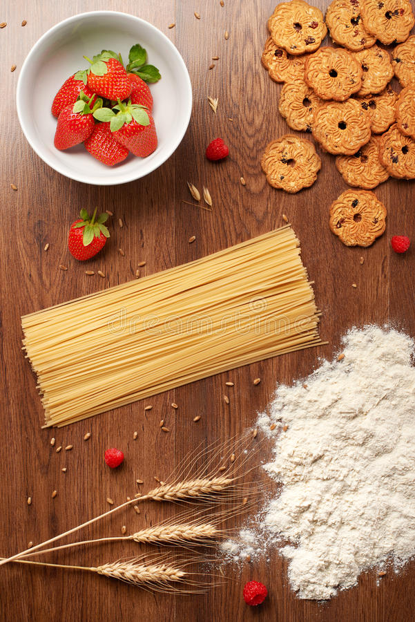 Droge spaghettideegwaren, bloem, tarwe, eigengemaakte koekjes en bessen royalty-vrije stock afbeeldingen