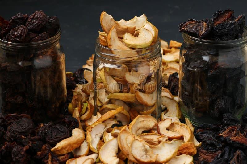 Droge vruchten in glaskruiken op donkere achtergrond stock foto's