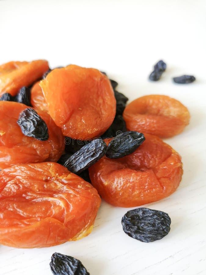 Droge vruchten rozijnen en droge abrikozen op een witte achtergrond stock foto's