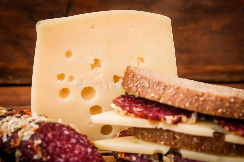 Droge worst en kaas met gaten voor ontbijt stock afbeeldingen