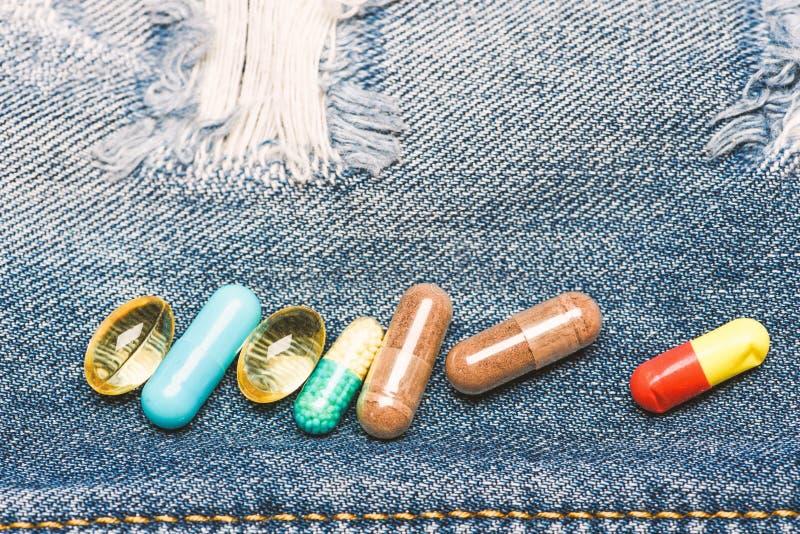 Drogen auf Denimhintergrund Set bunte Pillen Mischende Medizin Schnelle Behandlung Medizinverordnung Str?flinge und Arme lizenzfreie stockfotografie