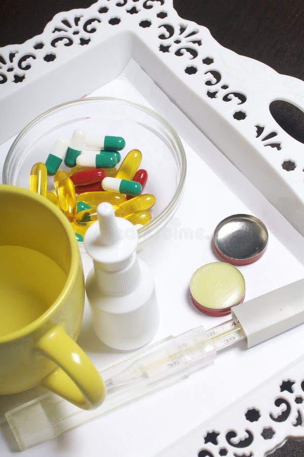 Drogen für Behandlung stehen auf einem weißen Behälter Pillen von verschiedenen Farben, Wasser in einem Becher und Nasenspray Auc lizenzfreie stockfotos