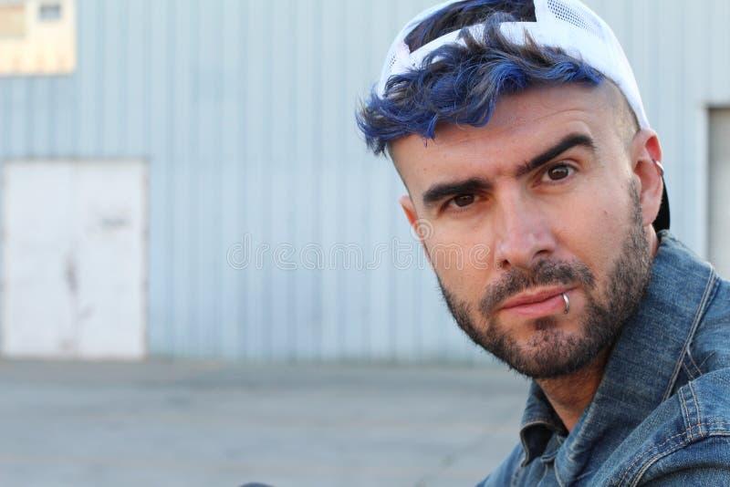 Drogen missbrukade rebelliska mannen för barn med blått dog hårsammanträde på misstänksam mörk grändväg med kopieringsutrymme royaltyfri foto