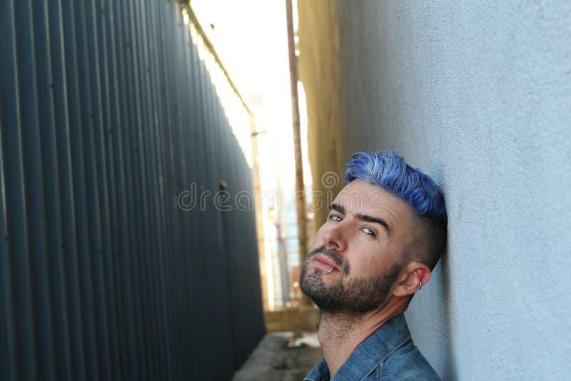 Drogen missbrukade rebelliska mannen för barn med blått färgade hårsammanträde på misstänksam mörk grändväg arkivbilder