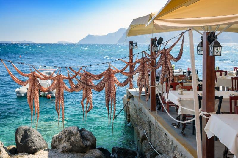 Drogende octopuswapens bij Griekse herberg op Santorini-eiland, traditionele Griekse die zeevruchten op een grill worden voorbere royalty-vrije stock afbeelding