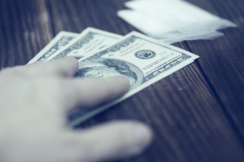 Drogenhandel, Verbrechen, Suchtabschluß oben der Hand mit Geld und Drogen Hand des Süchtigmannes mit Geldkaufendosis des Kokains  stockfotos