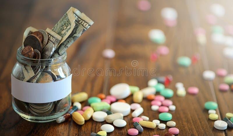 Droger och mynt i en glass krus på ett trägolv Fick- besparingar royaltyfri fotografi