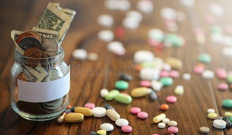 Droger och mynt i en glass krus på ett trägolv Fick- besparingar arkivfoton