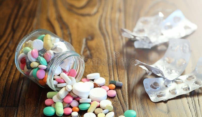 Droger och mynt i en glass krus på ett trägolv Fick- besparingar royaltyfria foton