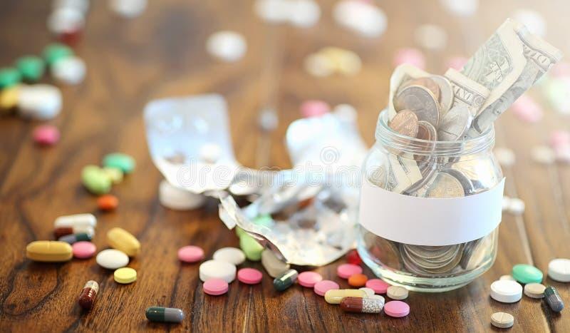 Droger och mynt i en glass krus på ett trägolv Fick- besparingar royaltyfri foto