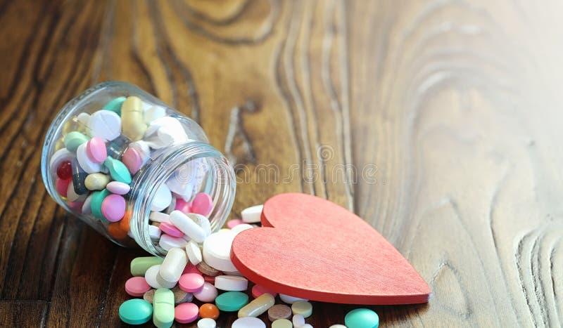 Droger och mynt i en glass krus på ett trägolv Fick- besparingar royaltyfria bilder