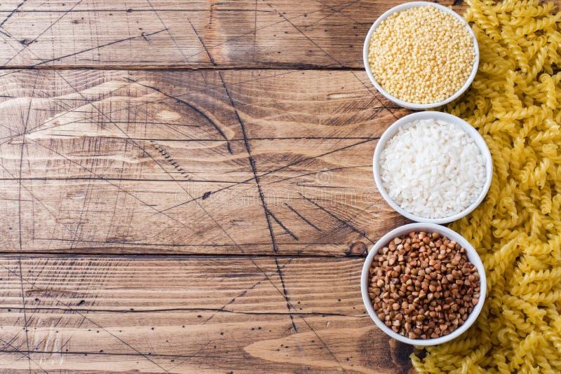 Drogheria asciutta dei chicchi Grano saraceno e miglio della pasta del riso sui precedenti di legno immagine stock libera da diritti