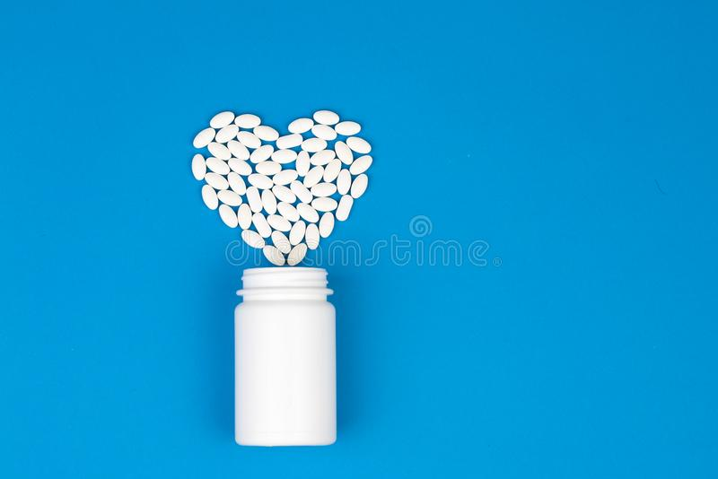 Droghjärtaform och flaska av preventivpillerar arkivbilder
