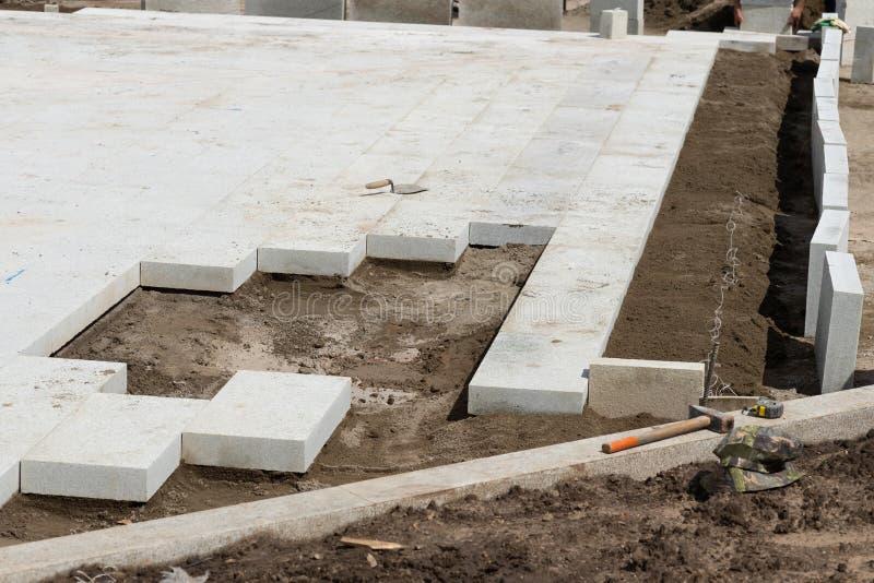 Drogowe pracy na ulicach Kamienie i brukowe cegiełki na ziemi Odbudowa na ulicach Naprawa chodniczki beton obrazy royalty free