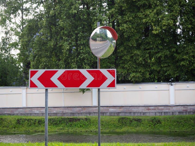 Drogowego ruchu drogowego mirrow i czerwony ruchu drogowego znak z dwa kierunkami dla jechać na tle lasowym i rzecznym obrazy royalty free