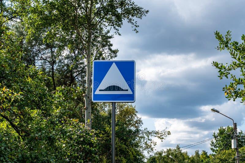 Drogowego znaka prędkości garbek na tle chmurny niebo i las fotografia royalty free
