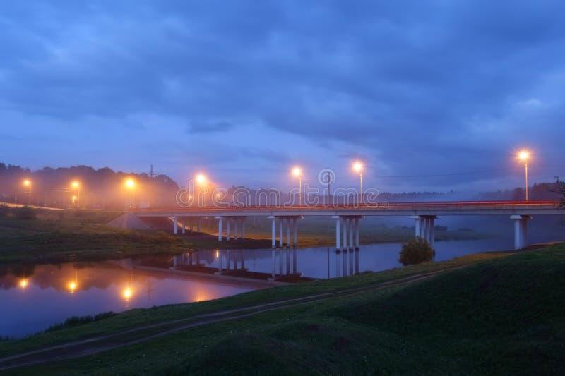 Drogowy most okrywający w mgle nad małą rzeką fotografia stock