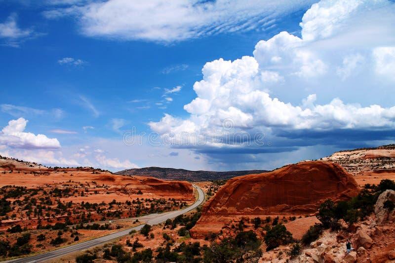 Drogowy omijanie przez wyginającego się, skalistego krajobrazu z odległymi burz chmurami w Utah, usa zdjęcie stock