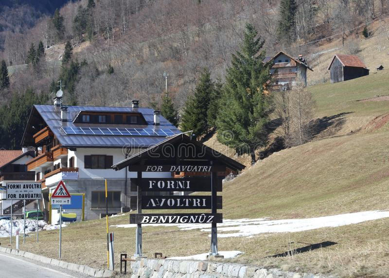 Drogowy znak wskazuje Włoskiego miasteczko dzwoniącego Forni Avoltri Wo zdjęcia stock