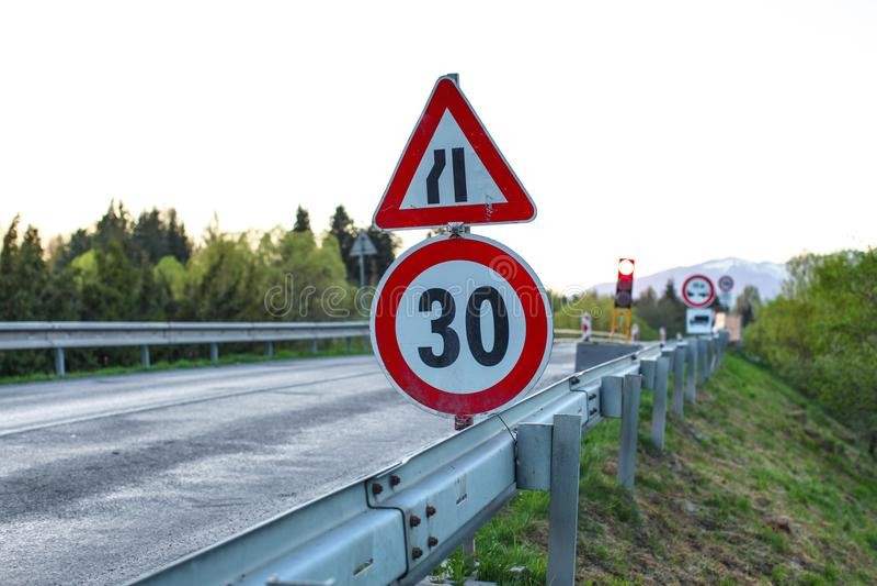 Drogowy znak, zmniejsza prędkość, zamazanego czerwonego światła ruchu i przeciw 30, obraz stock