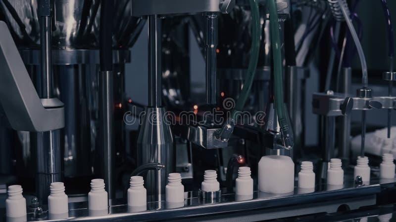 Drogproduktion Medicinska sm? medicinflaskor p? farmaceutisk tillverkningslinje Medicinska ampuller på automatiserad produktionsl royaltyfri foto