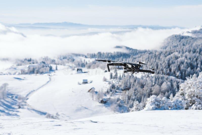 Drohnenfliegen über einem Berg bedeckt mit Schnee lizenzfreie stockfotografie