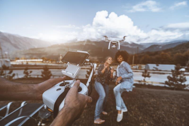 Drohnensendung von zwei Mädchen, Betreiber ` s Hände im Vordergrund lizenzfreie stockfotografie
