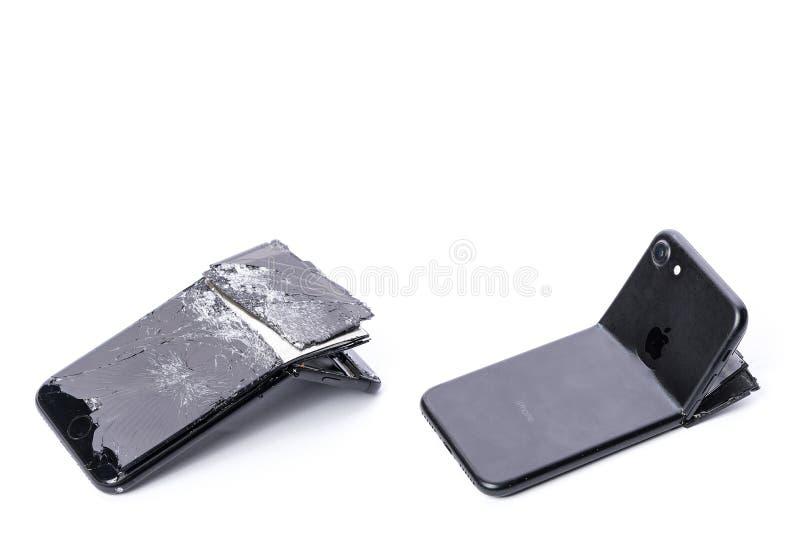 Drohobych, Ucraina - 1° novembre 2017: iPhone 7 con lo schermo rotto e la copertura indietro piegata, su fondo bianco con ombra fotografie stock libere da diritti
