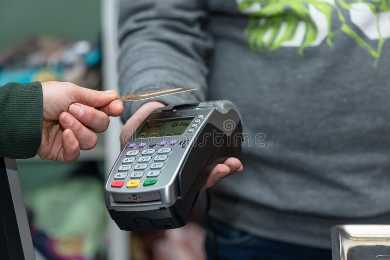 Drohobych, Ukraine - November 18, 2018: Client do payment with contactless credit card in pet shop. Credit card reader implements royalty free stock images