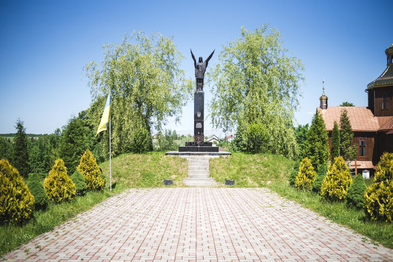 Drohobych, Western Ukraine - June 3, 2017: Monument of Fame to the fighters for freedom of Ukraine and ancient wooden ch royalty free stock photo