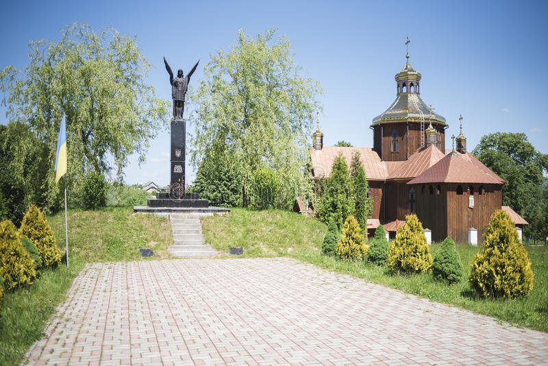 Drohobych, Western Ukraine - June 3, 2017: Monument of Fame to the fighters for freedom of Ukraine and ancient wooden ch. Located in Nyzhni Hayi Village stock photography