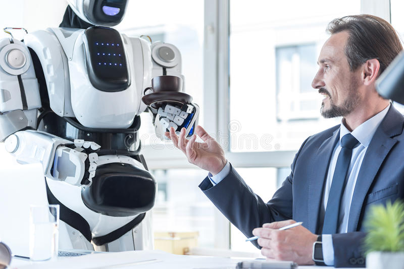 Droid está trayendo el café para el hombre de negocios agradable imágenes de archivo libres de regalías