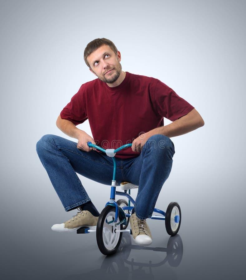 Dromen van een mens op een fiets van kinderen stock foto