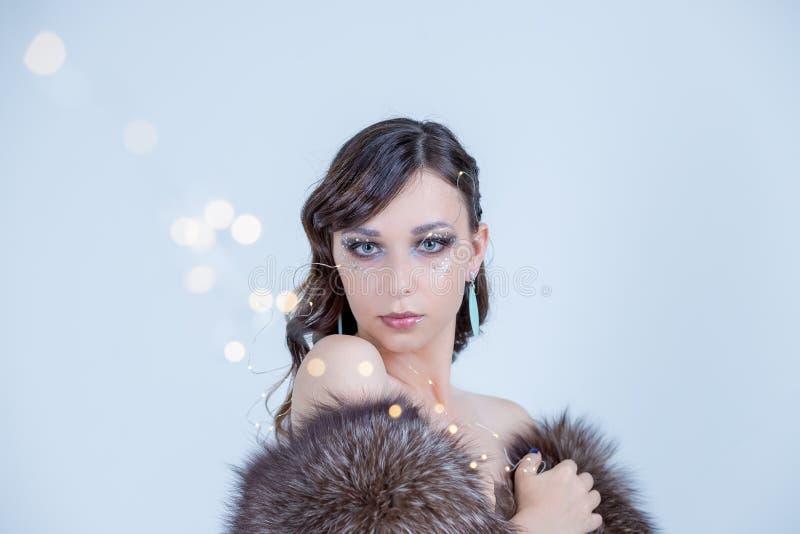 Dromende de wintervrouw het omhooggaand en dragen die bonthoed kijken Het manierportret van mooi sexy vrouwenmodel met creatief m stock foto