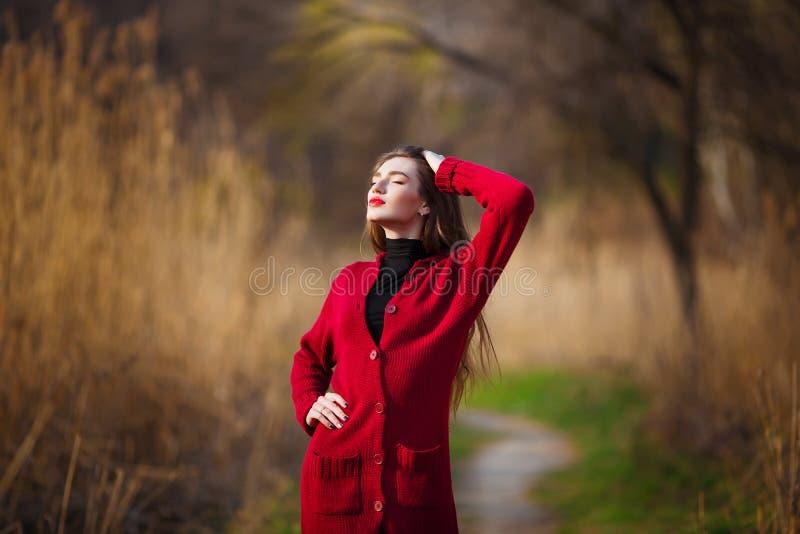 Dromende jonge vrouw Mooi wijfje die met lang gezond haar van aard in park genieten die rode cardigan dragen De lente royalty-vrije stock foto's