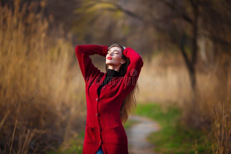 Dromende jonge vrouw Mooi wijfje die met lang gezond haar van aard in park genieten die rode cardigan dragen De lente royalty-vrije stock afbeelding
