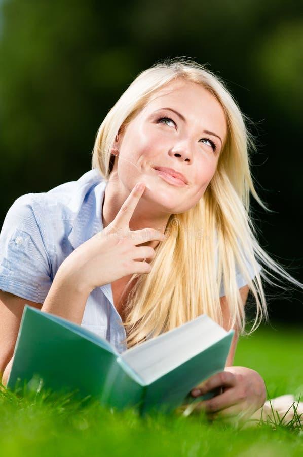 Dromende vrouw die op gras en het lezen van boek liggen stock afbeeldingen