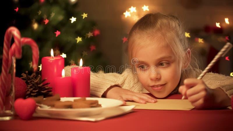 Dromerig meisje die over haar wensen aan Kerstman, het schrijven brief, kinderjaren denken stock fotografie
