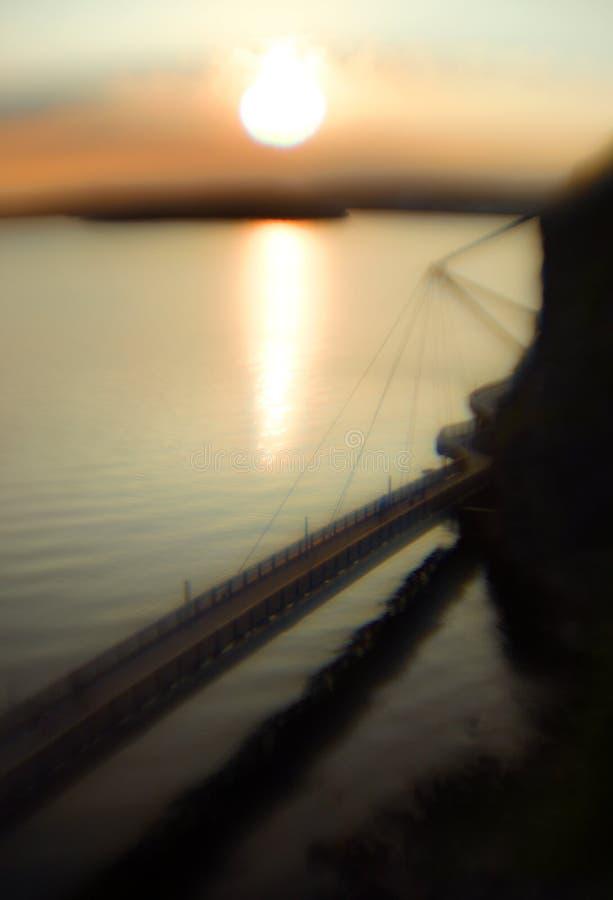 Dromerig zacht beeld van een het lopen brug door de oceaan tijdens zonsondergang stock foto