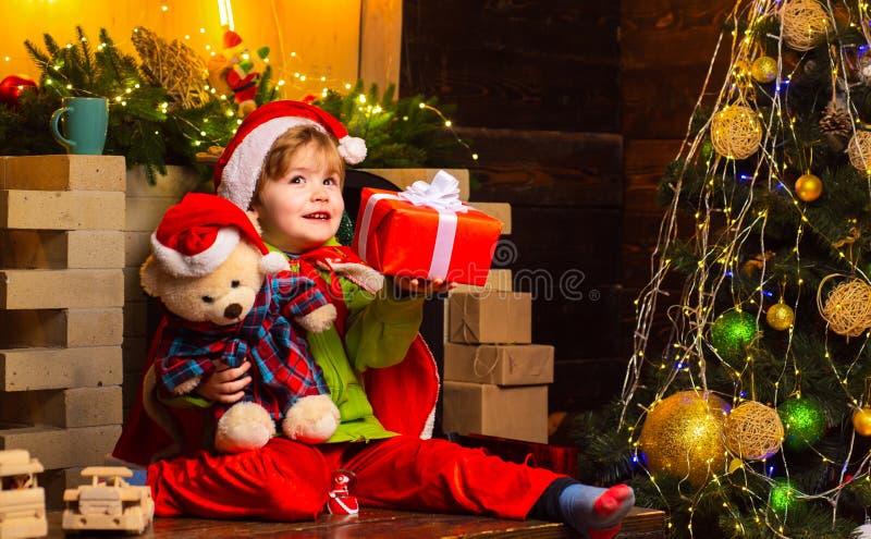 Dromerige babypeuter op Kerstmisvooravond Geloof in Kerstmismirakel Wens om de Kerstman te ontmoeten De vakantie van de winter vr stock foto