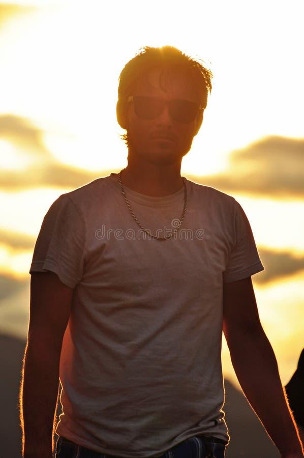 Dromerige hete knappe jonge mens als achtergrond in zonsondergang royalty-vrije stock foto's