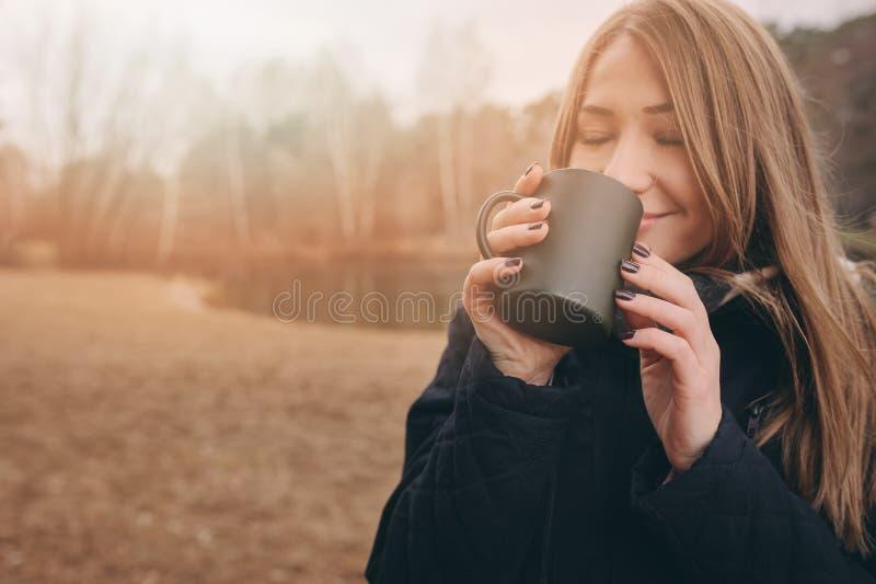 Dromerige jonge vrouw die hete thee openlucht op de gang drinken, die van het reizen in de herfst genieten royalty-vrije stock afbeelding