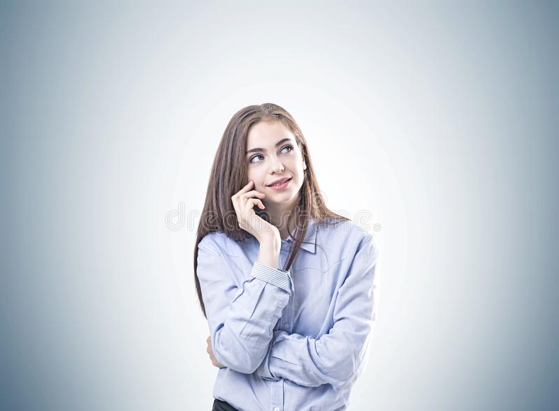 Dromerige jonge vrouw in een blauw grijs overhemd, royalty-vrije stock fotografie