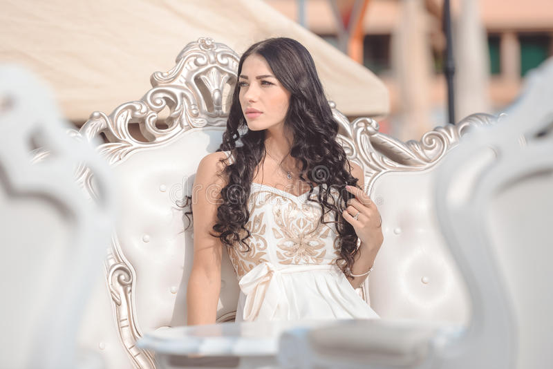 Dromerige mooie damezitting op gebogen luxe stock foto
