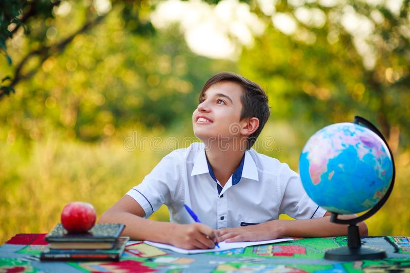 Dromerige schooljongenleerling die bij een lijst in een tuin in openlucht bestuderen stock afbeelding