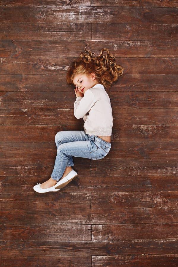 Dromerige stemming Meisje omhoog het krullen, het liggen op de vloer, het kijken weg en het glimlachen royalty-vrije stock foto