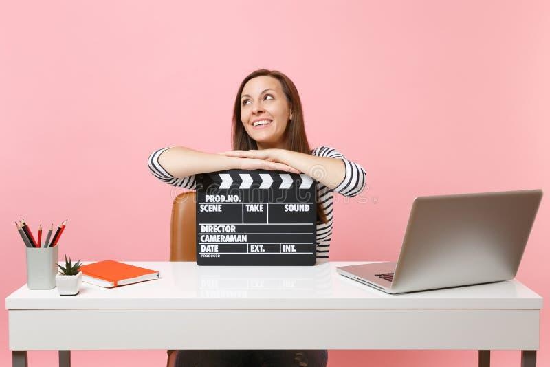 Dromerige vrouw die omhoog mager op klassieke zwarte film die clapperboard en aan project werken terwijl het zitten op kantoor ma royalty-vrije stock afbeeldingen