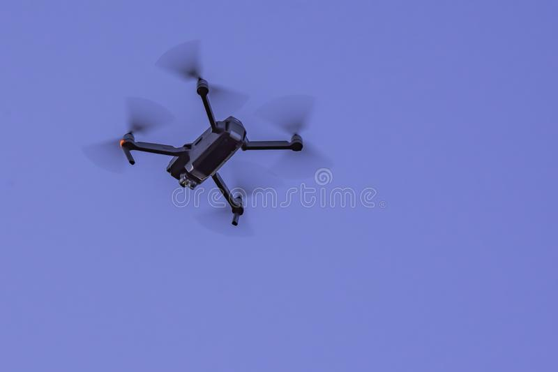 Drone in action. Black camera drone in flight with visible propelers movement and flashing light on blue sky background stock images